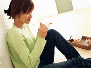 お茶をのんで床に座る女性