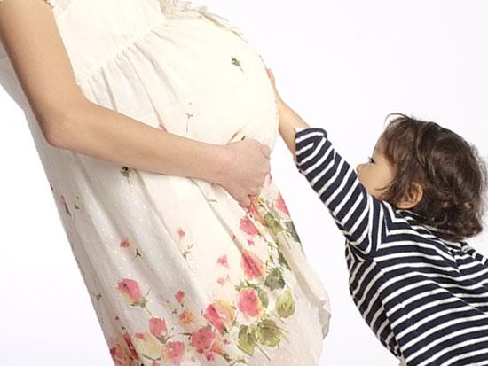 妊婦のお腹に触る子供