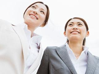 スーツを着た女性が二人並んでいる。