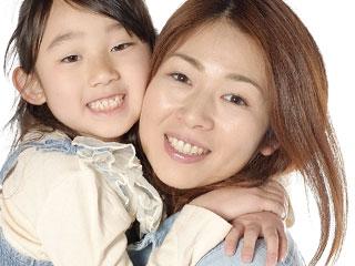 母親の首に手を廻して抱きつく子供