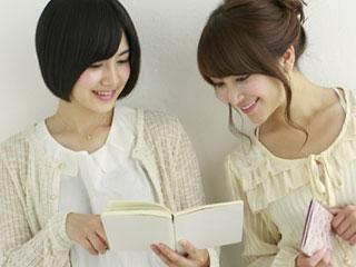 開いたノートを相手の女性に見せる女性