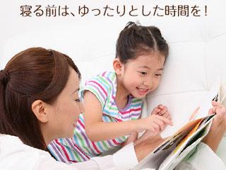 子供に絵本を見せている母親