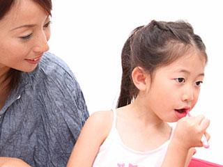 歯磨きする子供と見守る母親