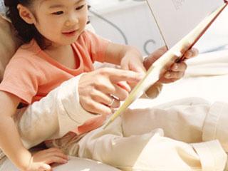 親の膝の上で絵本を見る子供