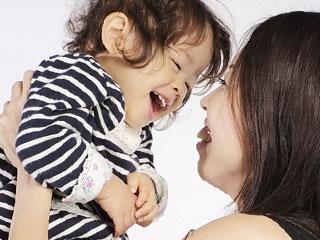 抱き上げた子供に顔を近づける母親