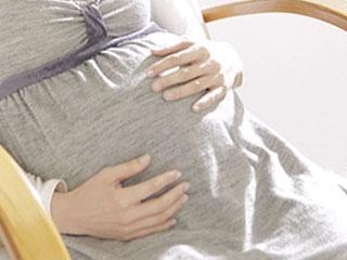 妊婦がお腹を触っている