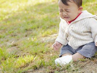 芝の上に座り込んで泣く赤ちゃん