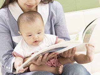 赤ちゃんに絵本を読んであげる母
