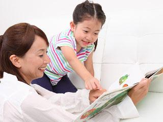 絵本を開いて子供に見せる母親