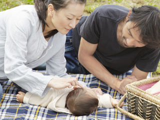 芝生でシートの上で寝る赤ちゃん