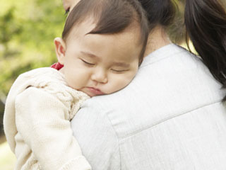 散歩する母親の肩で寝る赤ちゃん