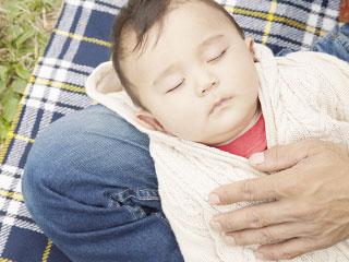 公園で親の膝の上で寝る赤ちゃん