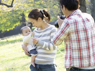 公園で赤ちゃんを連れて散歩する両親