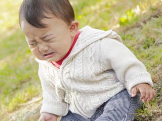 公園の芝生の上で泣いている赤ちゃん