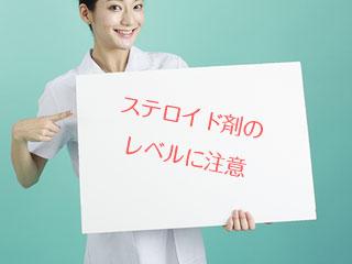 看護師が注意喚起のパネルを持つ