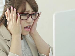 仕事しながら顔をしかめる女性