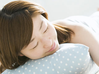 横になって安らかな表情の女性
