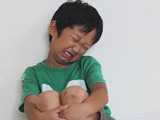 膝を抱えて痛がる子供