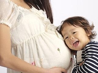 妊婦のお腹に耳を当てる子供