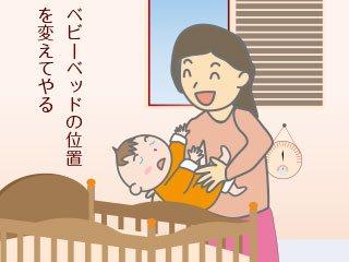 ベビーベッドに赤ちゃんを寝かせる母親
