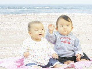 砂浜に座る二人の赤ちゃん