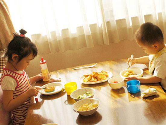 兄弟で向かい合って食事する子供