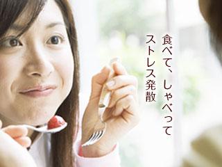 友人と食事する女性