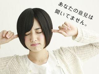 耳を塞ぎながら目を閉じる女性