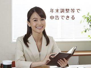 手帳を見ながら机に向かう女性