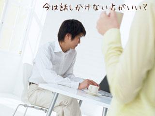 ノートパソコンを見る夫と近づく妻