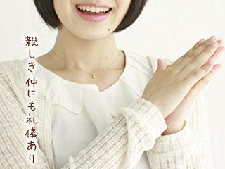 両手を合わせて笑顔の女性
