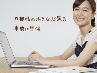 本を傍らにパソコン見る女性
