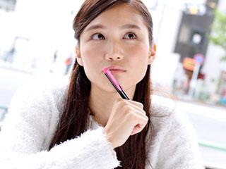 ペンを口に当てて思案する女性