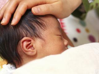 赤ちゃんの頭に手を当てる親