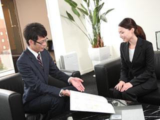 会社で書類を見ながら話す女性