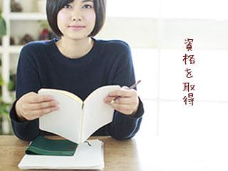 机に向かい本を開く女性