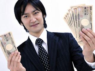 万札を両手に持つスーツ姿の男性