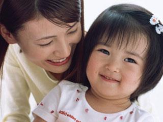 子供に笑顔で話しかける母親