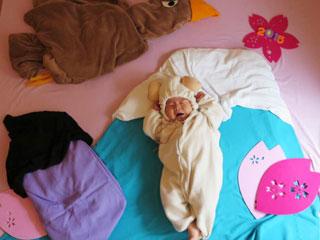 カラフルな寝具の真ん中で眠る赤ちゃん
