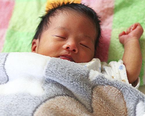 布団をかけられた仰向けで寝る赤ちゃん