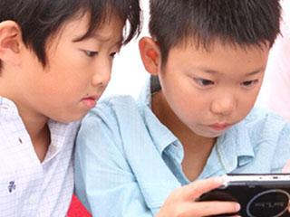ゲームする兄弟を隣で見つめる男の子