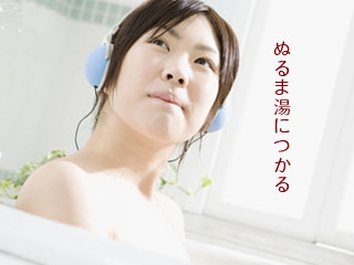 浴槽に入りながらヘッドホンをする女性