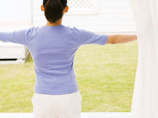 カーテンを開けて陽射しを浴びる女性
