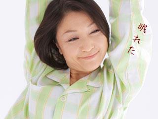 パジャマ姿で体を伸ばす女性