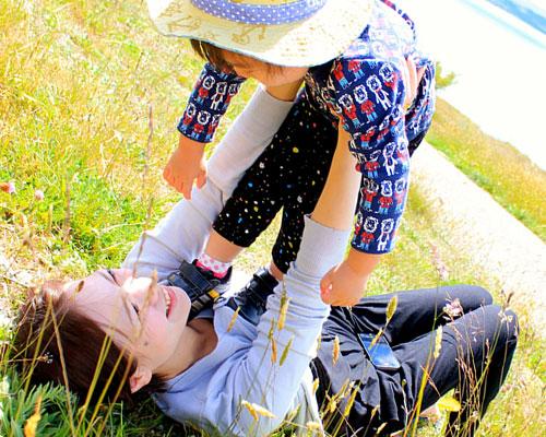 草地で子供を抱えてあやす母親