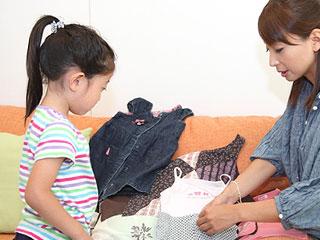 子供の前で服の組み合わせを見せる母親