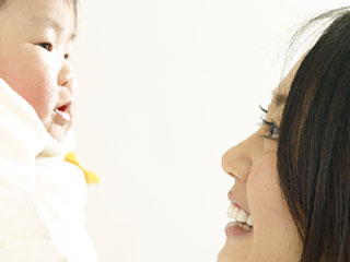 赤ちゃんを見つめながら笑う母親