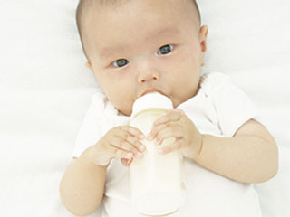 哺乳瓶を両手掴んでミルクを飲む赤ちゃん