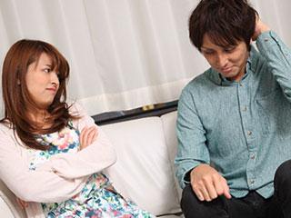 女性に隣に座って頭を掻く男性