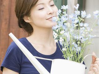 鉢植えの花を運ぶ女性